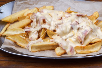 French fries with bacon under cheese sauce